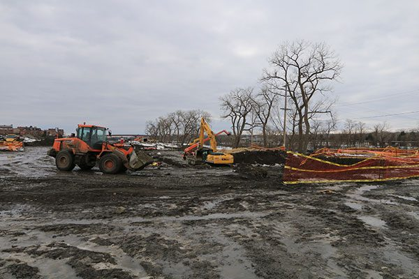 Backhoe moves soil for Starbuck Island foundation project