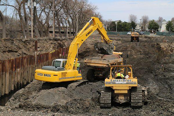 Exacavator loads soil into a dump truck