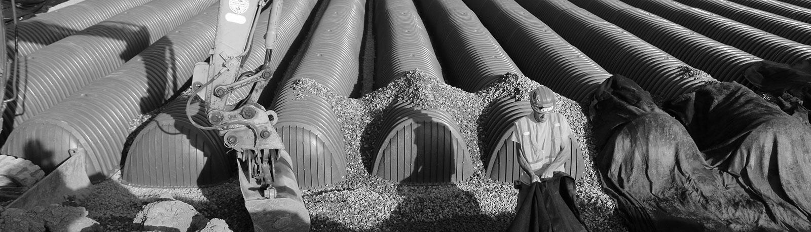 Man in hard hat stands in front of large pipes in ground - black and white