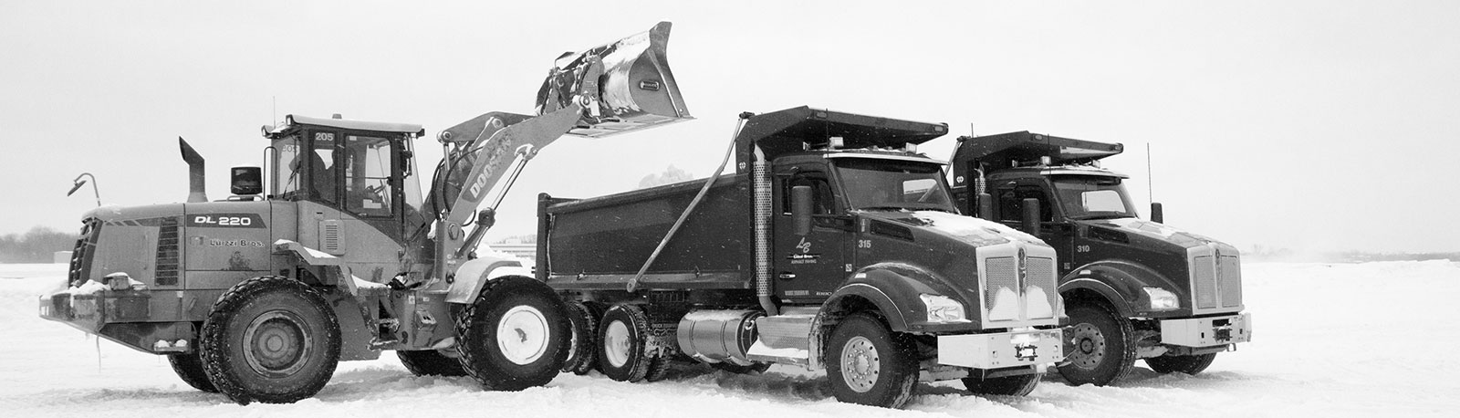 Backhoe empties snow into a Luizzi Bros dump truck_ black and white