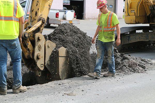 Workers in hard hat stand by as excavator removes soil from trench in road