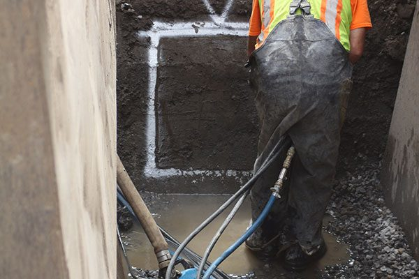 Worker uses hydraulic tool to cut through cement