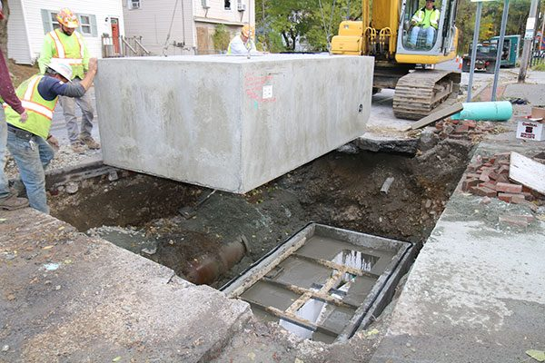 Cement block is lowered into hole in roadway