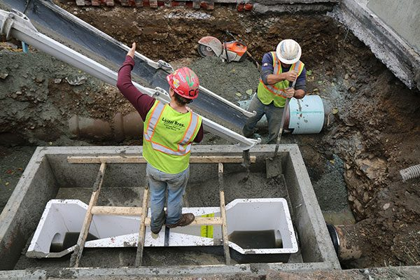 Cement is poured as part of a sewer meter replacement project