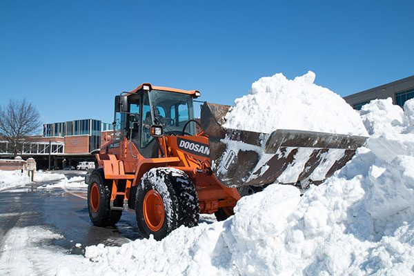 Backhoe operator removes a bucket of snow at Albany County Airport