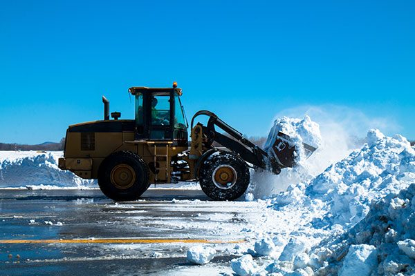 Backhoe removes a bucket of snow in a parking lot