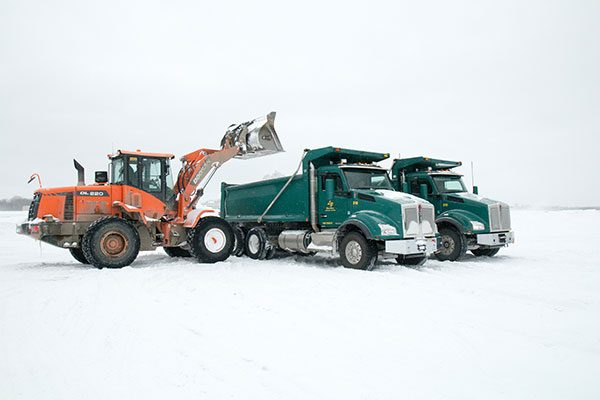 Backhoe empties snow into a Luizzi Bros dump truck
