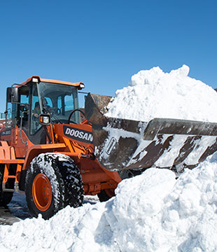Front loader with bucket full of snow