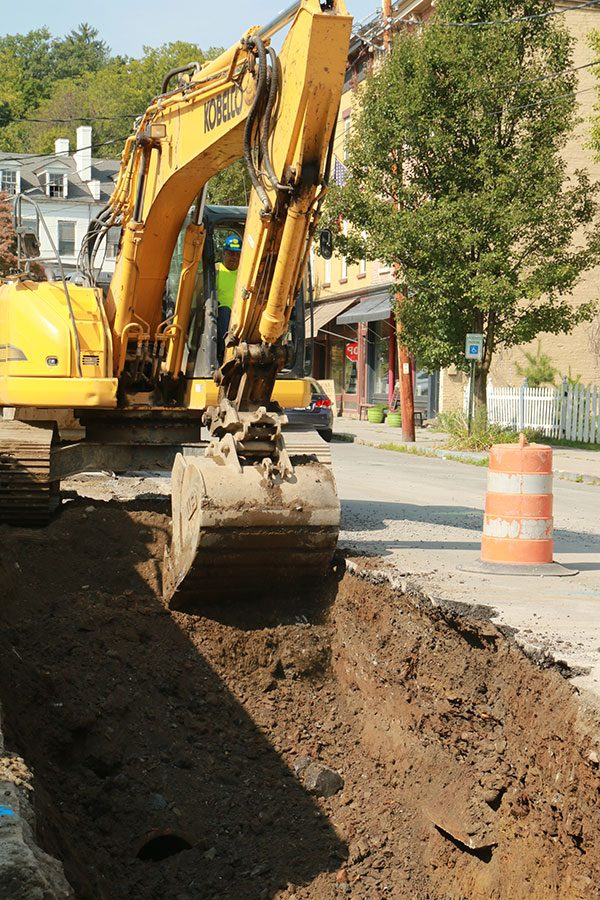 Excavator digs in trench on Main Street in Coxsackie