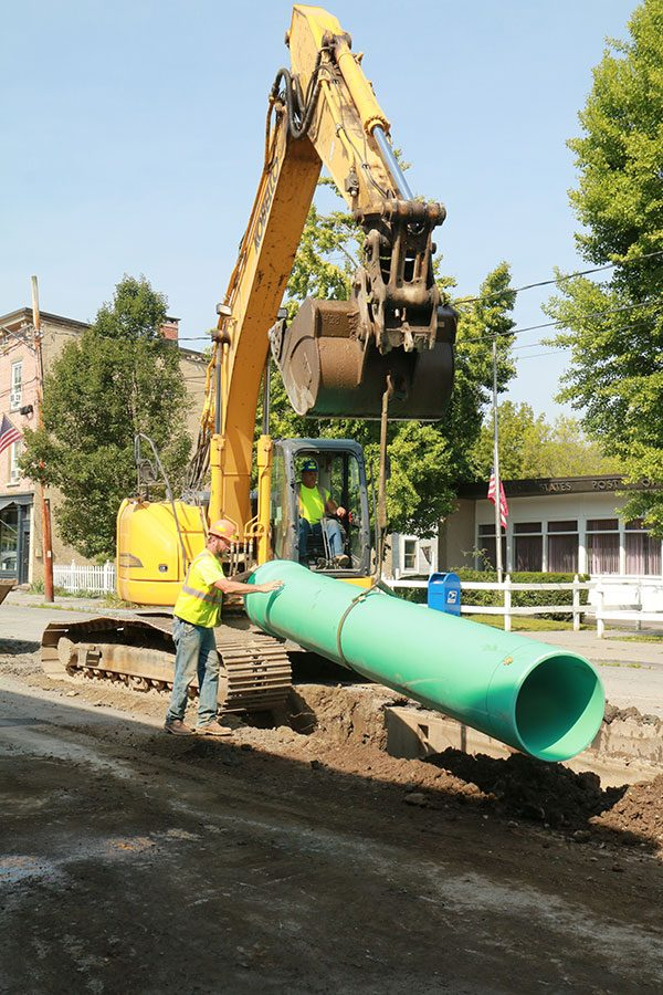 Construction worker guide new sewer pipe into the trench