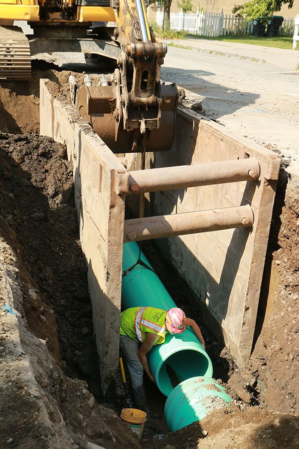 Construction worker in trench replaces sewer pipe