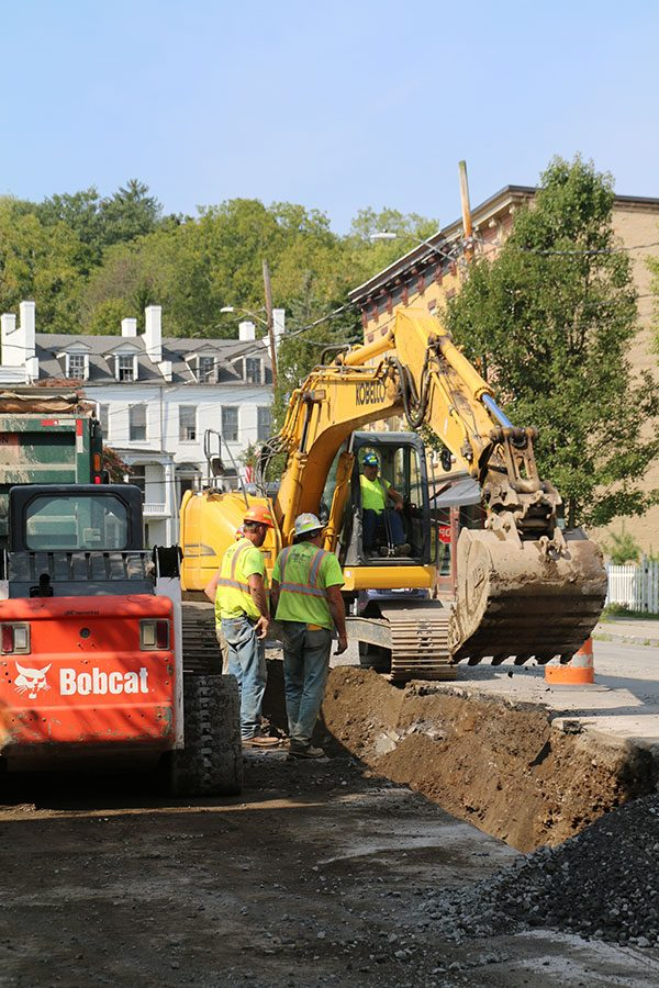 Luizzi Bros workers in hard hats watch as excavator digs trench in road