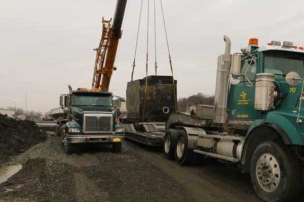 Crane placing the PRV vault on the lowboy truck