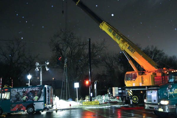 Rented crane holding the PRVVault in the hole at night