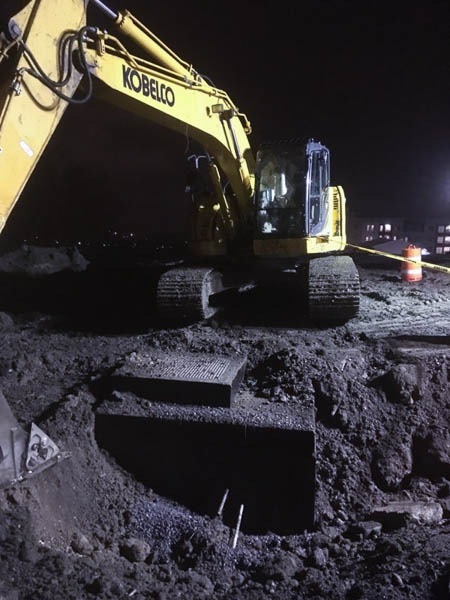 Excavator sitting above the newly dug hole