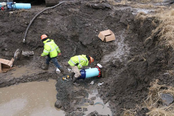 two workers prepping the water main pipe