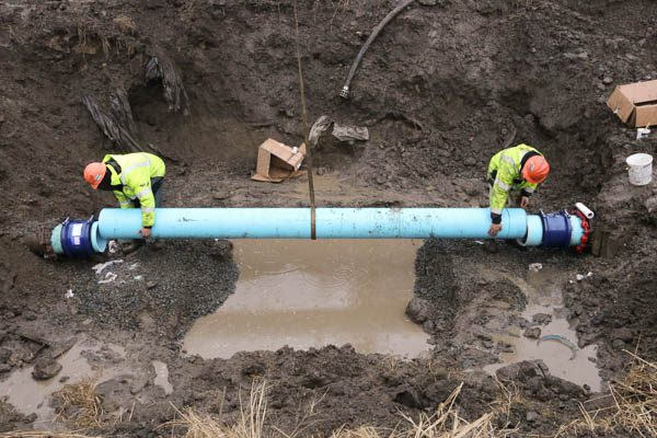 Two workers placing the new pipe on the open ends