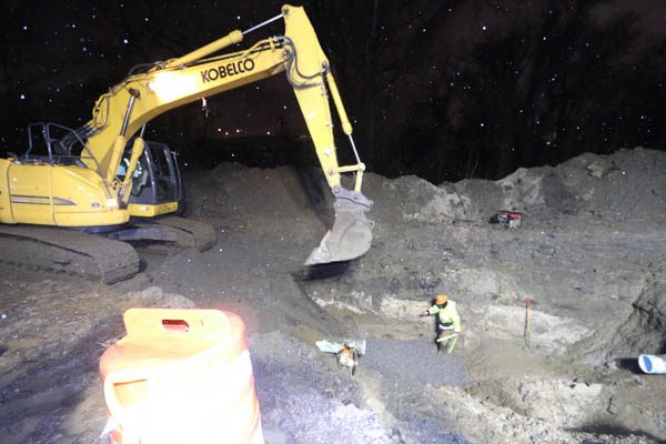 Excavator digging a hole for the vault