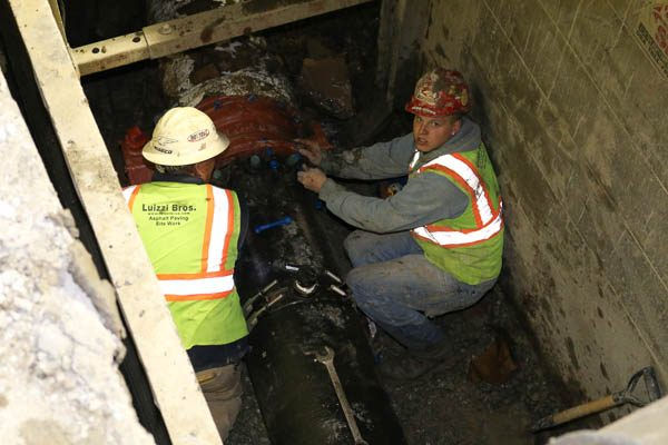 Two workers in the trench attaching new water main