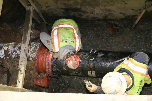 Worker fastening new water main pipe