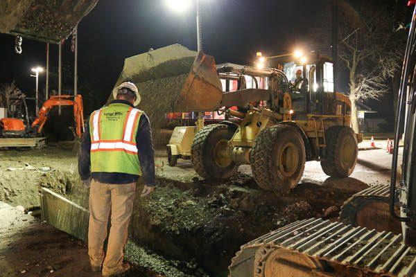 Worker watching a loader dump gravel