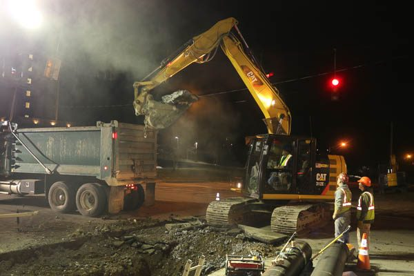 Excavator removing asphalt and placing into a dump truck