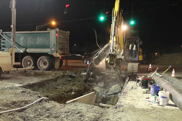 Excavator removing asphalt pieces
