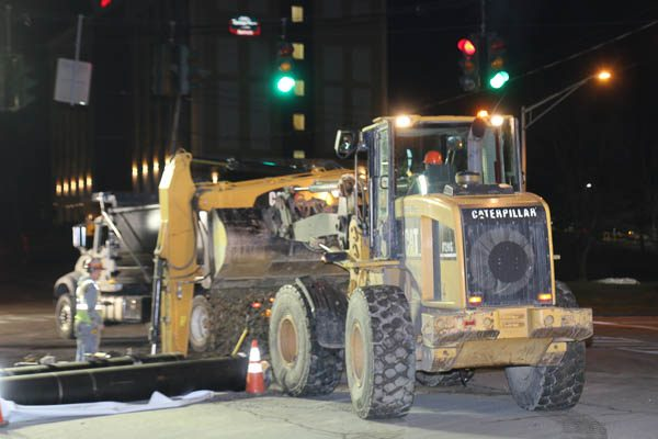 Construction equipment surrounding the open hole in the road