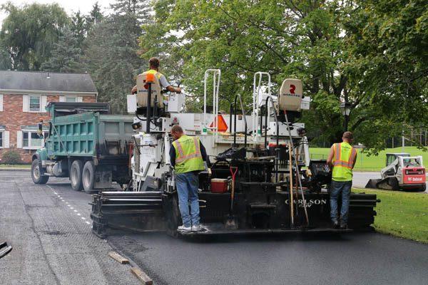Presidential Estates paving crew smoothing asphalt