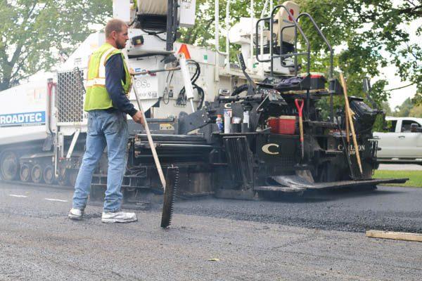 Presidential Estates laborer raking asphalt