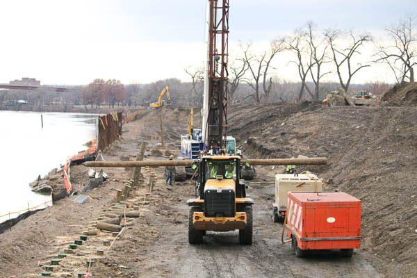 Excavator carrying timber piles