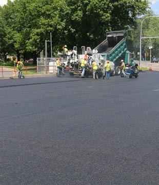 Dump truck loading asphalt into the paver
