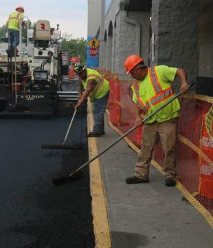 Workers smoothing asphalt