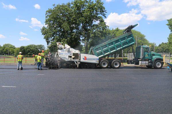 Dump truck pouring asphalt into a paver