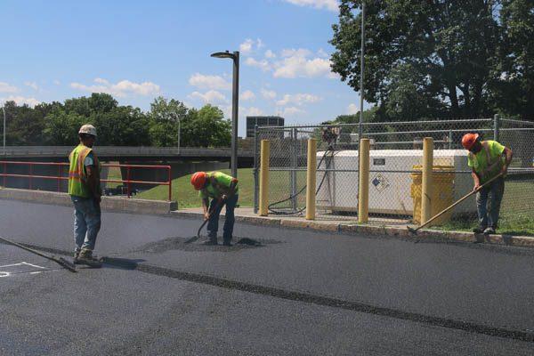 laborer shoveling asphalt