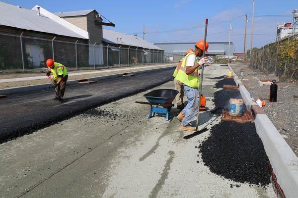 laborers smoothing asphalt