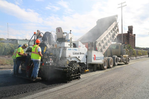 Dump truck emptying asphalt to the paver